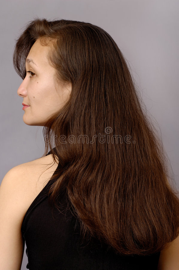 Girl with long brown hair. Beautiful young woman face and long brown hair portrait royalty free stock image