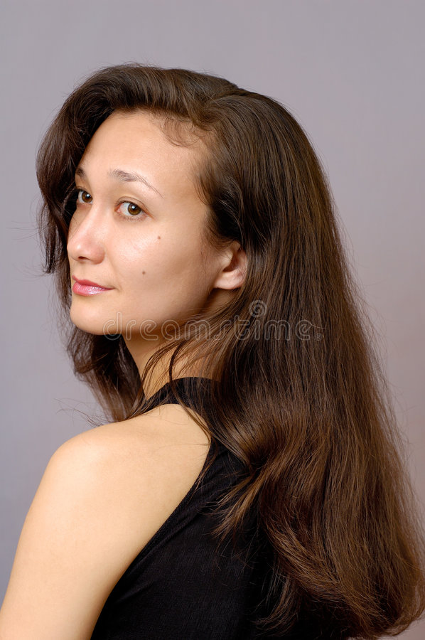 Girl with long brown hair. Beautiful romantic young asian woman face portrait stock image