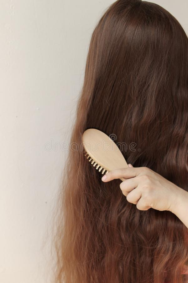 Girl with long brown hair combing them with a wooden comb, vertical, close-up stock image