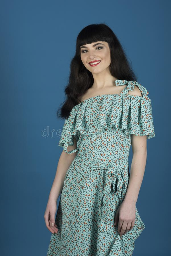Girl with long brunette hair wears cerulean dress. stock photography