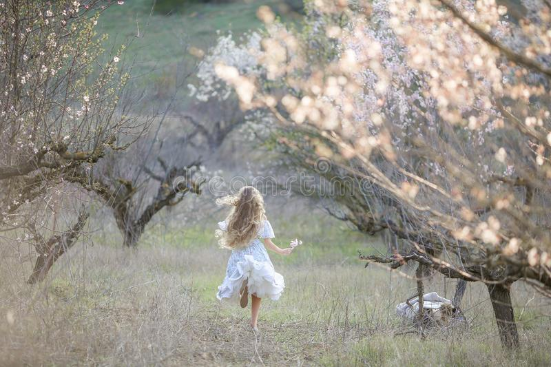 A girl with long curly blond hair. Dancing in the blossoming garden. Pure nature royalty free stock photo