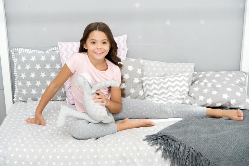 Girl long curly hair enjoy evening time with favorite toy. Kid sit bed and play bunny toy modern bedroom interior. Evening time. Girl child wear pajamas play royalty free stock photography