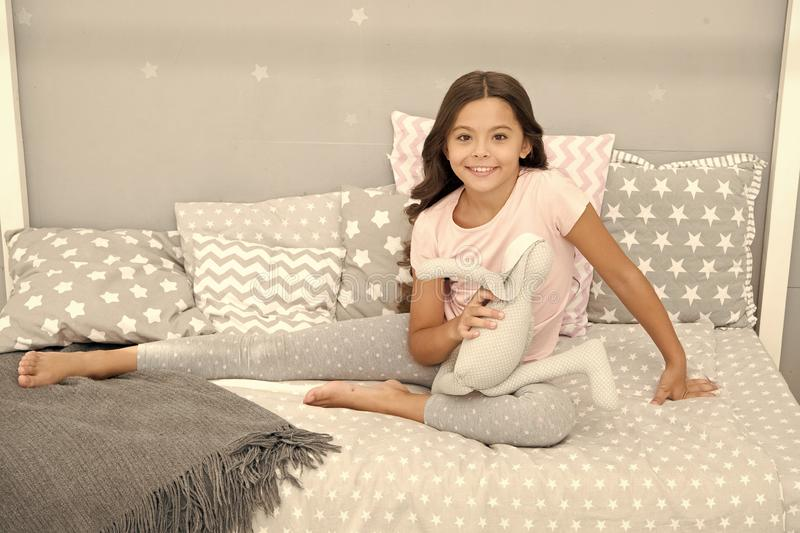 Girl long curly hair enjoy evening time with favorite toy. Kid sit bed and play bunny toy modern bedroom interior. Evening time. Girl child wear pajamas play royalty free stock image