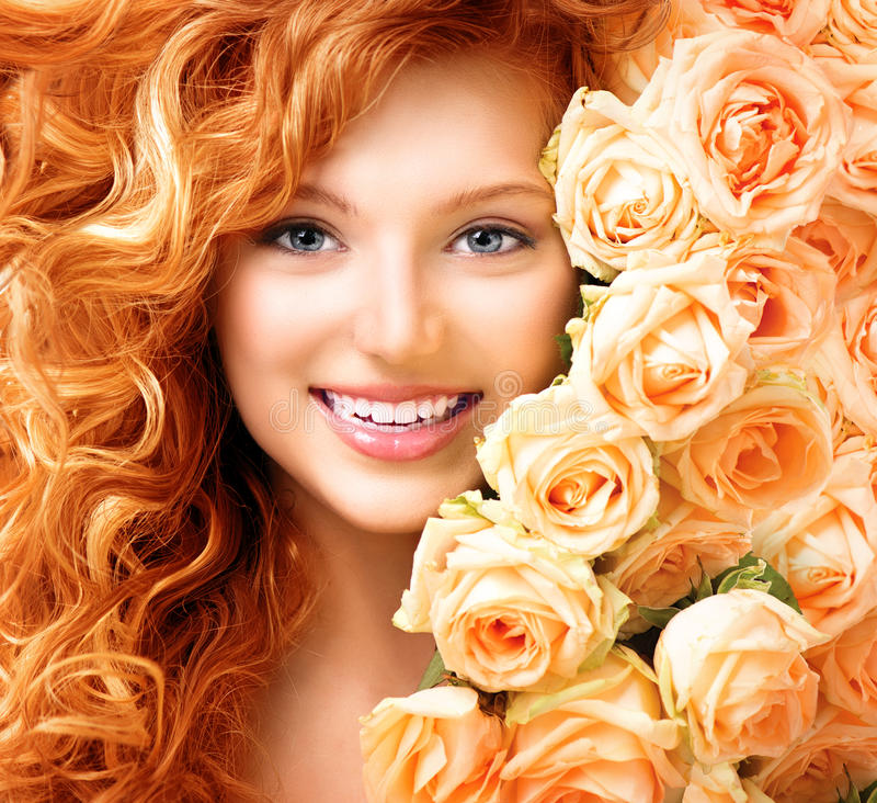 Girl with long curly red hair. And beautiful roses stock photo