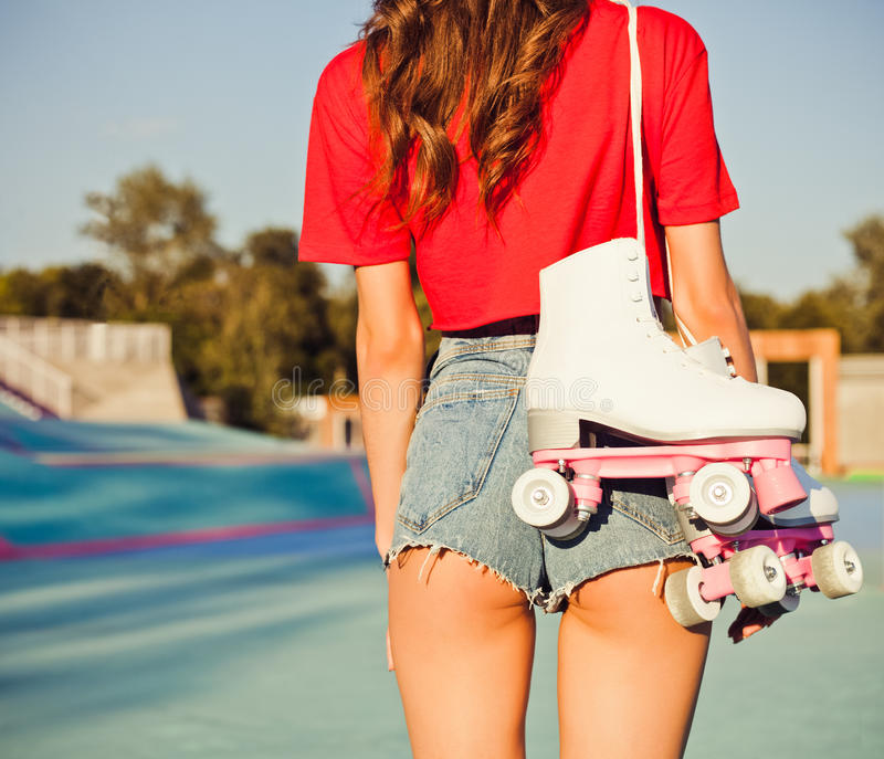 Girl with long dark hair is back with white roller skates on her shoulder. Warm summer evening in the skate park. Outdoor. Close royalty free stock photo