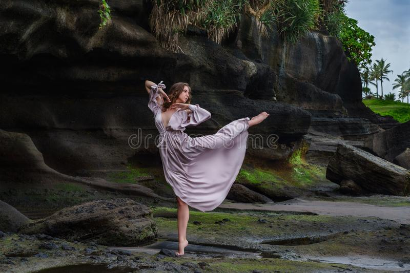 Girl in long dress is gently posing in dance in arabesque on ocean beach in time low tide in nature background. Elegant young woman in beautiful long dress with royalty free stock photo