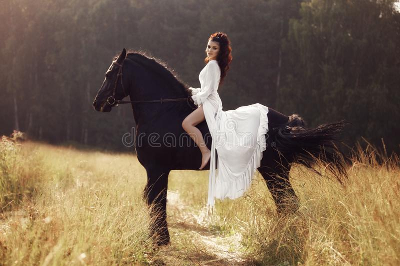 Girl in a long dress riding a horse, a beautiful woman riding a horse in a field in autumn. Country life and fashion, noble steed.  royalty free stock photography