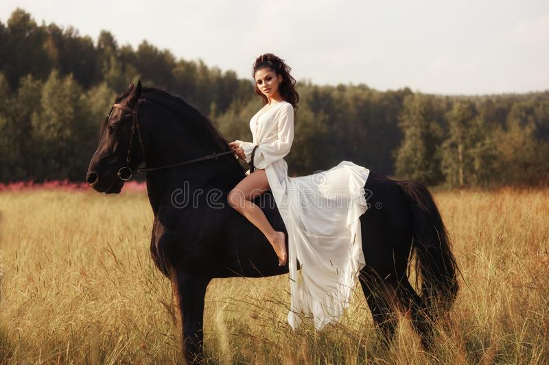 Girl in a long dress riding a horse, a beautiful woman riding a horse in a field in autumn. Country life and fashion, noble steed.  royalty free stock images