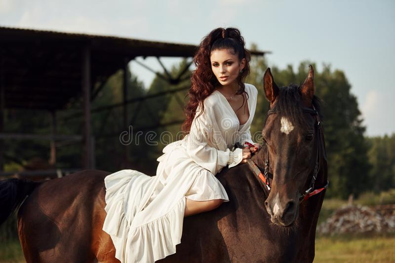 Girl in a long dress riding a horse, a beautiful woman riding a horse in a field in autumn. Country life and fashion, noble steed.  stock photo