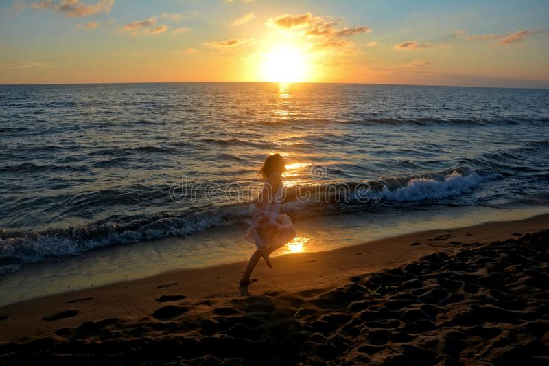 Girl in the long dress runs at the sundown along the beach stock images