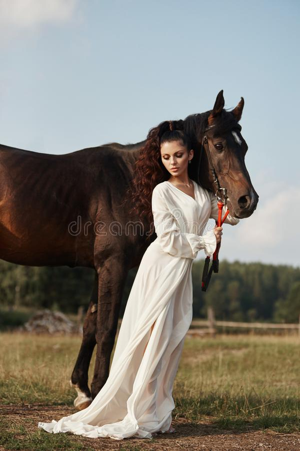 Girl in a long dress stands near a horse, a beautiful woman strokes a horse and holds the bridle in a field in autumn. Country. Life and fashion, noble steed stock photos