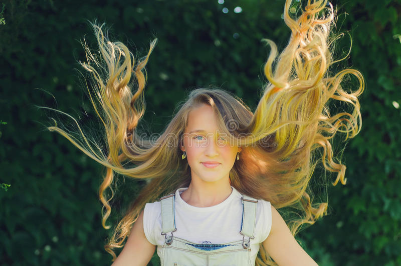 Girl with long fly blond hair. Portrait of a beautiful girl with long fly blond hair, the sun is shining on her hair. Attractive young woman enjoying her time stock photos
