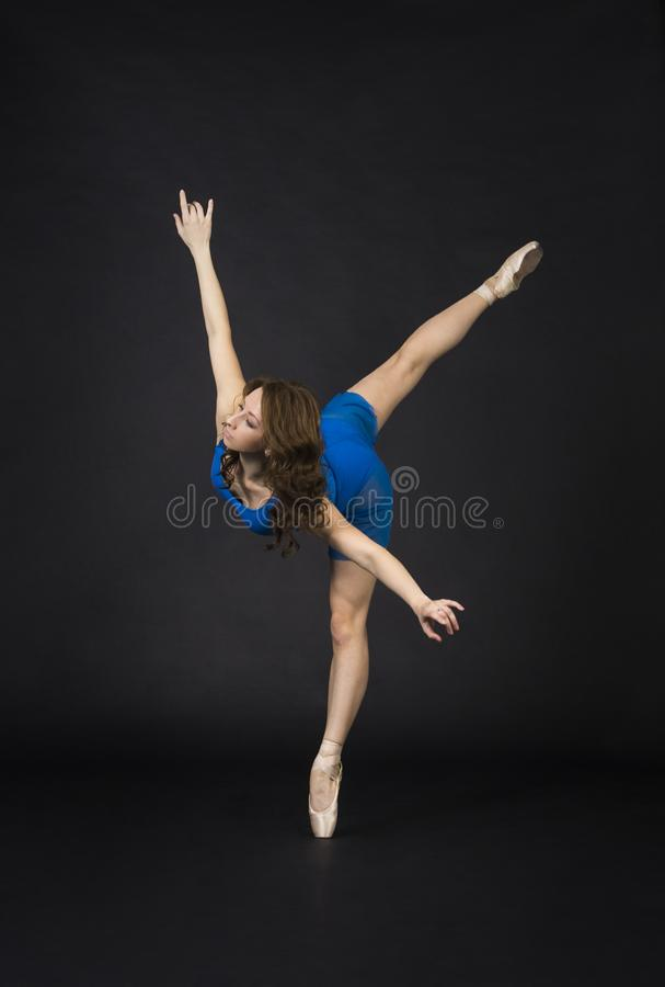 A girl with long hair, in a blue dress and Pointe shoes, dancing ballet stock photo