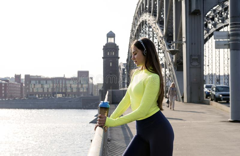 Girl with long hair in a green sports top stands on the bridge at sunset, a girl with a bottle of water in her hands on the bridge. Sports girl with long hair in royalty free stock photo