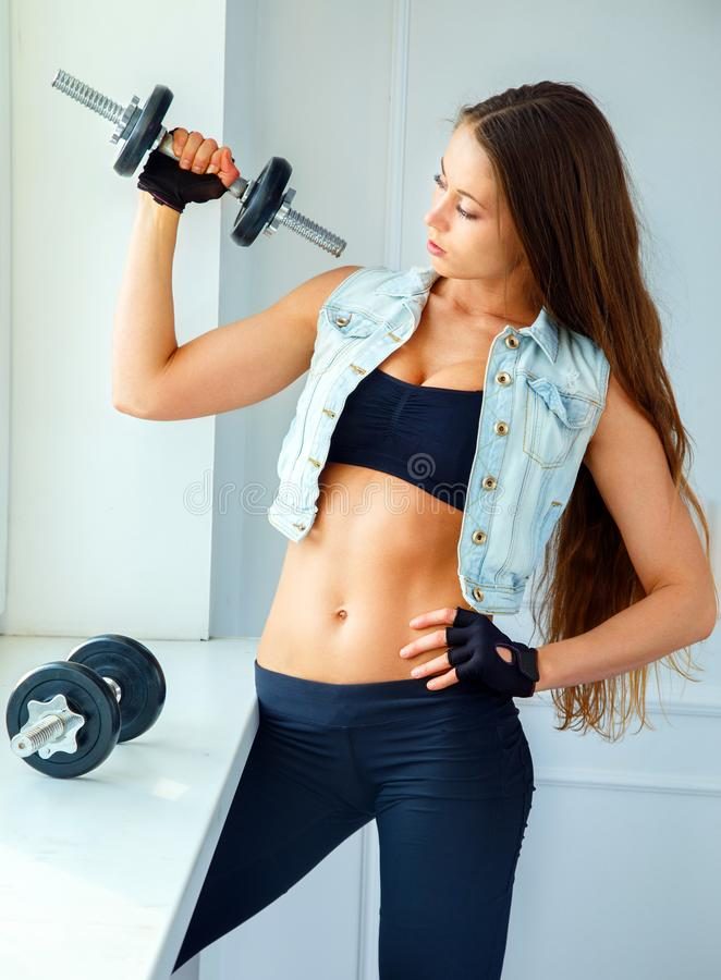 Girl with long hair holding dumbells. Girl with long hair posing with dumbells near window royalty free stock image