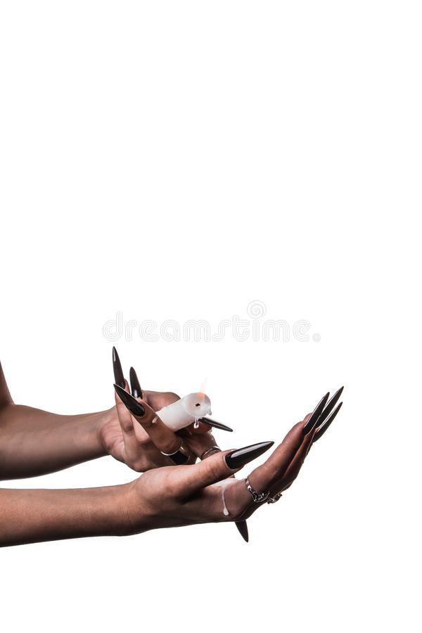 A girl with long hair in the image of a witch is trying to set herself on fire. rituals with candles for love spell and damage. Expulsion of a bad spirit from stock photos