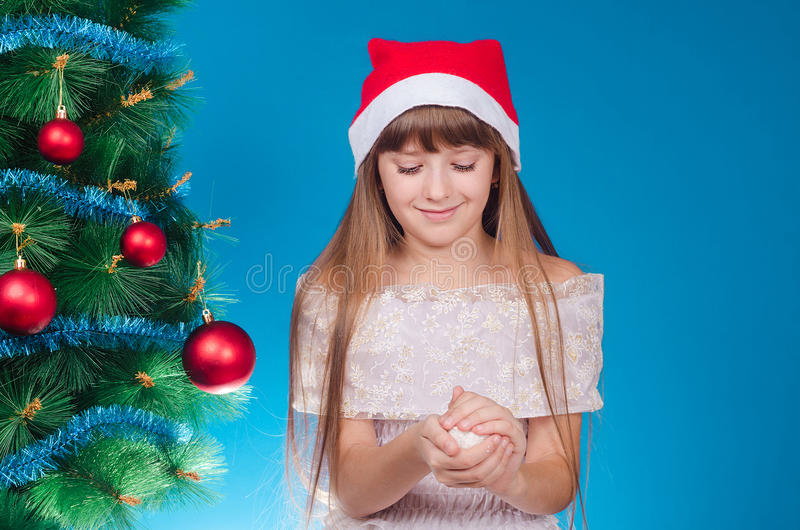 The girl with long hair in a red cap costs near a New Year tree. And does a snowball. New year. Christmas royalty free stock photo