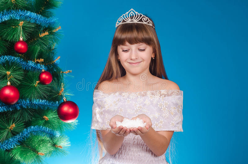 The girl with long hair in a red cap costs near a New Year tree. And holds in hand snow. New year. Christmas royalty free stock images
