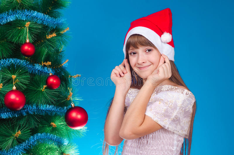 The girl with long hair in a red cap costs near a New Year tree. And smiles. New year. Christmas royalty free stock photo