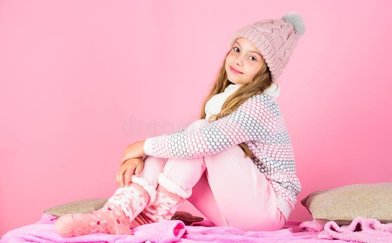 Girl long hair relaxing pink background. Winter fashion for children. Kid smiling fashion model. Kid girl wear cute stock image