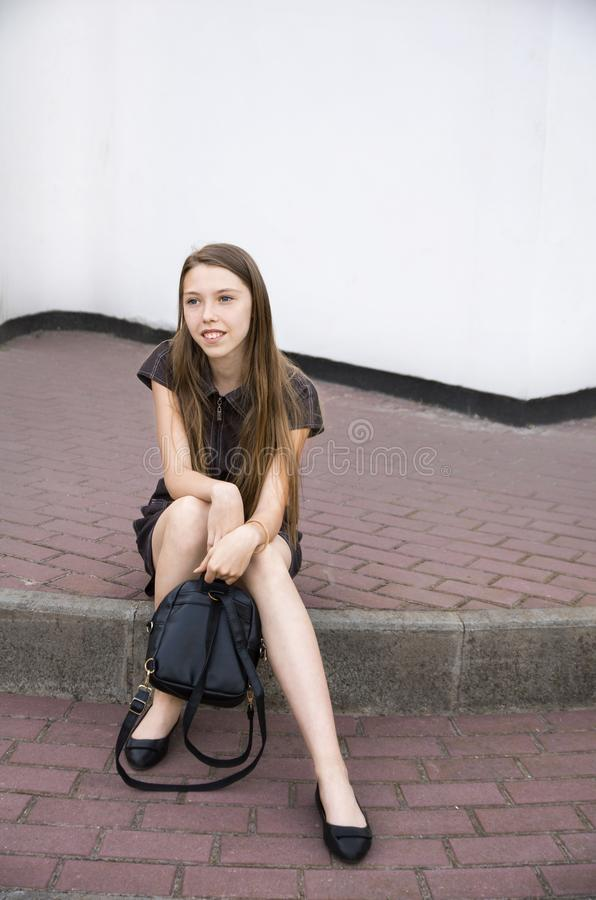 Girl with long hair sitting on the steps and holding a bag. Adolescence royalty free stock photos