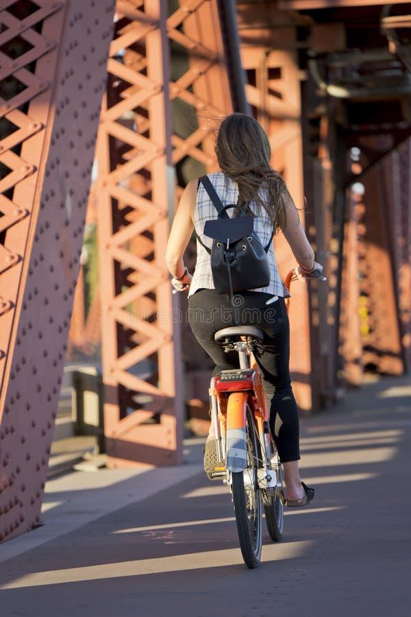 Slender girl with backpack rides bicycle on drawbridge stock image