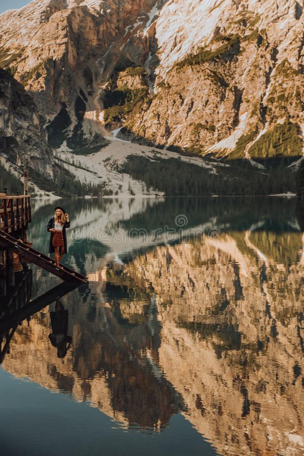 The girl with long hair wearing a wide-brimmed hat and a shirt striped on a background of Lake Lago di Braies in the royalty free stock images
