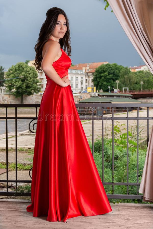 Girl in long red dress with hand on hips posing on the garden balcony on a wooden floor. Beautiful woman in long red dress with hand on hips posing on the garden royalty free stock photos