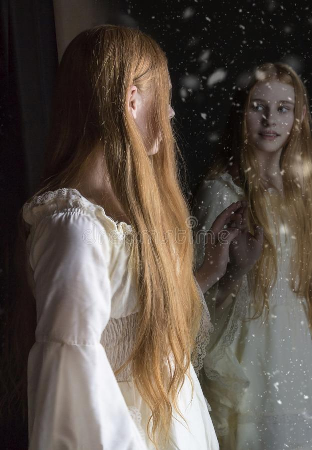 Girl looking in mirror. Girl with long red hair looking into a alternate world in the mirror royalty free stock images