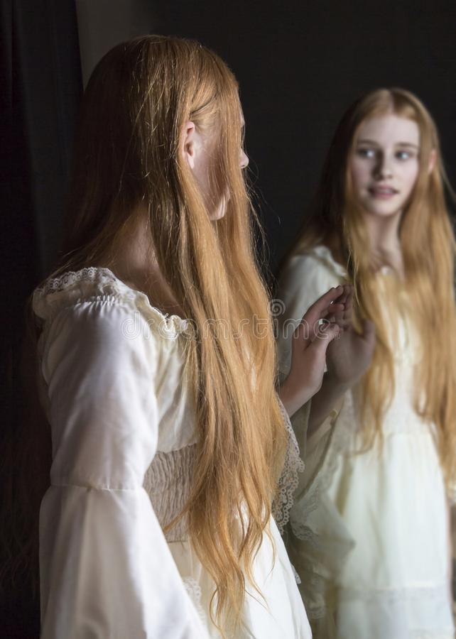 Girl looking into mirror. Girl with long red hair looking into mirror stock photo