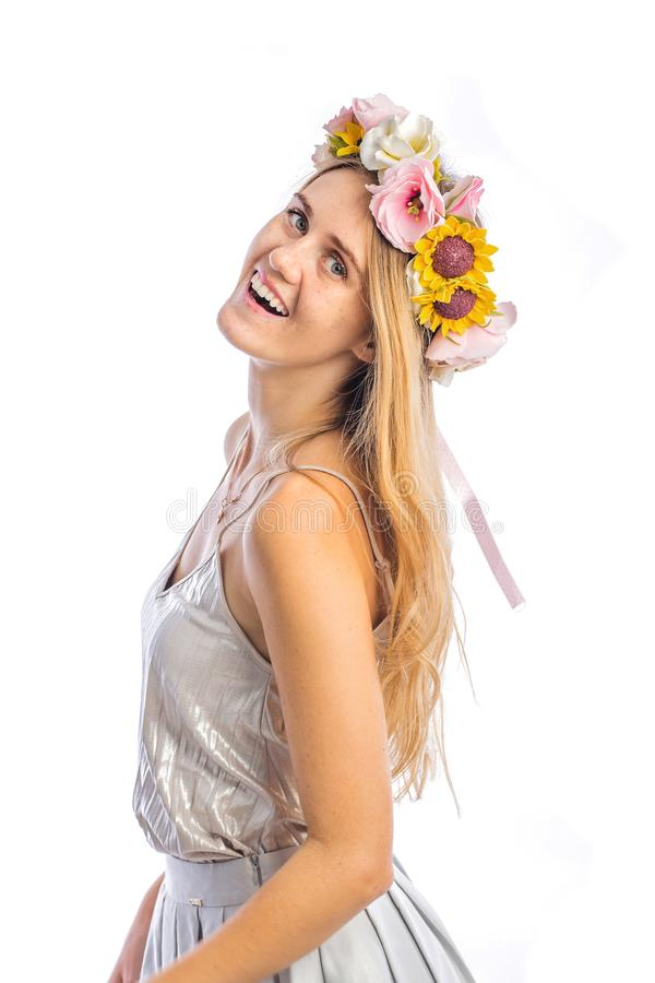 Girl with long red hair in a spring dress with flowers in her hair with smile is dancing on isolated background stock images