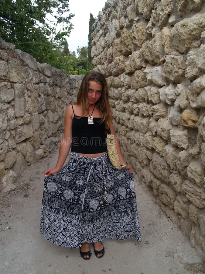 Girl in a long skirt smilinig near stone wall royalty free stock photography