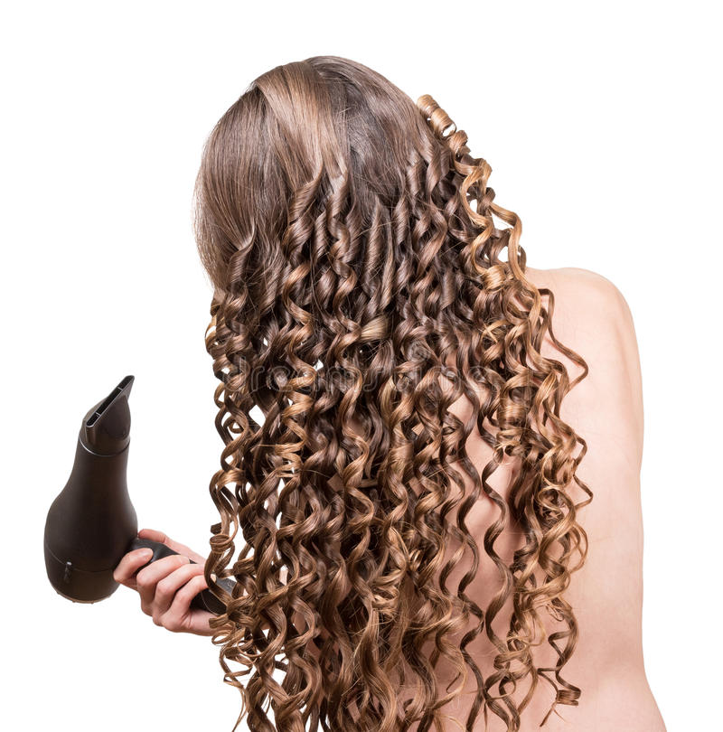 The girl with long wavy hair, hairdryer in hand isolated. stock photos