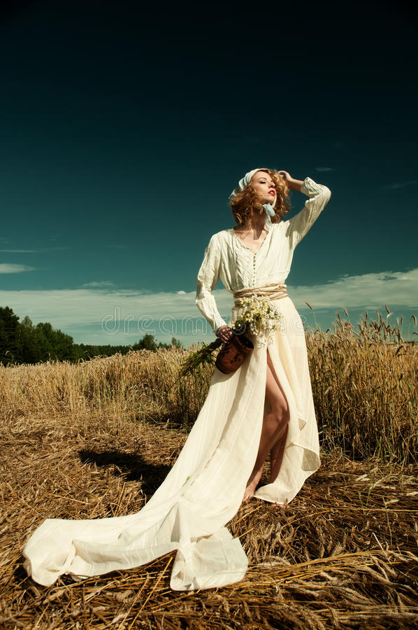 Girl in a long white dress in field of rye royalty free stock image