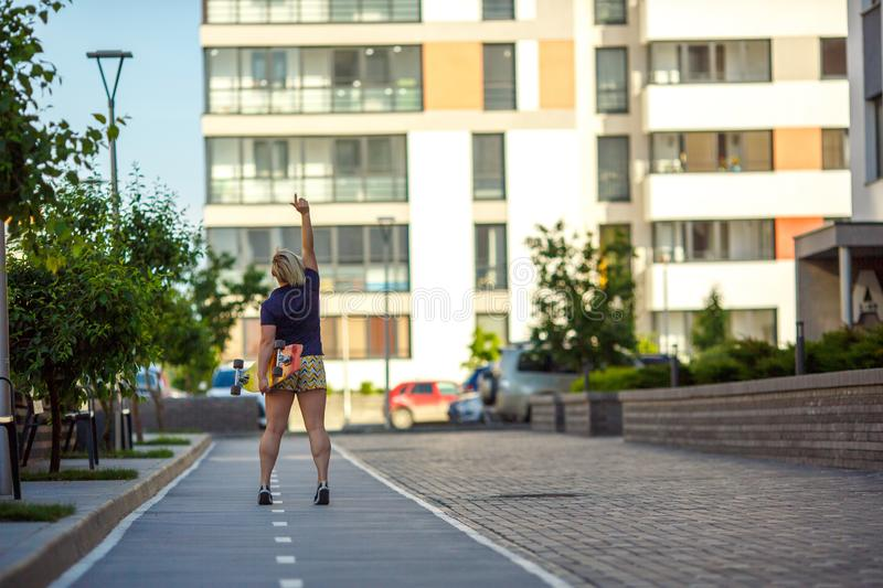 Girl with a longboard stands back, hand raised up royalty free stock images