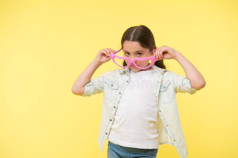 Girl look in heart shaped glasses on yellow background. Little child with fashion accessory. Keep calm and wear cool stock photography