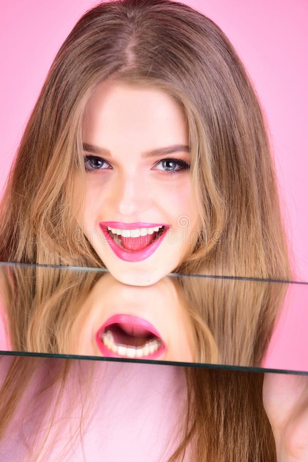 Girl look at mirror as multifaceted personality. Hairdresser salon and makeup concept. Healthy teeth and skincare of royalty free stock photography