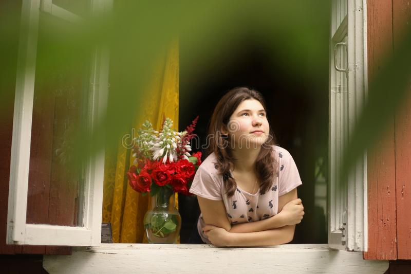 Girl look out of the window at morning from cottage summer house stock image