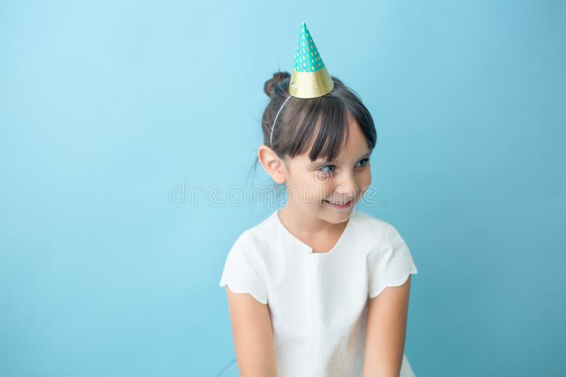 Playful girl with party hat. Girl is looking away. She is wearing a party hat. She is happy stock images