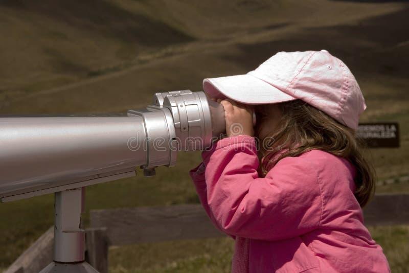 Girl looking with binoculars stock photography