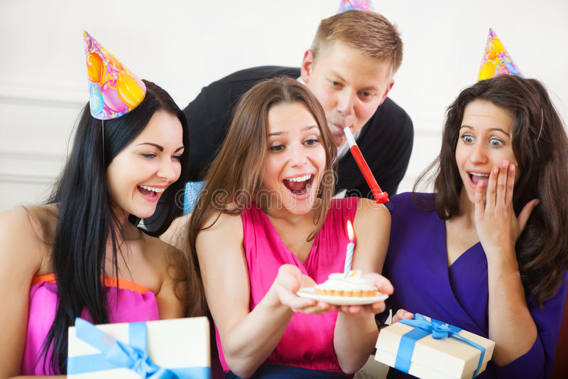 Girl looking at birthday cake surrounded by friends at party. Portrait of joyful girl looking at birthday cake surrounded by friends at party stock photos