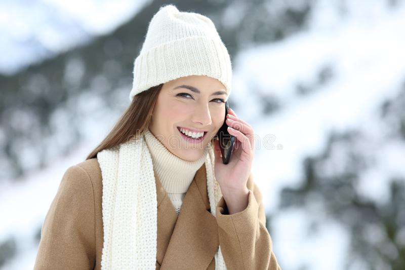 Girl looking at camera having a phone talk in winter. In a snowy mountain stock image