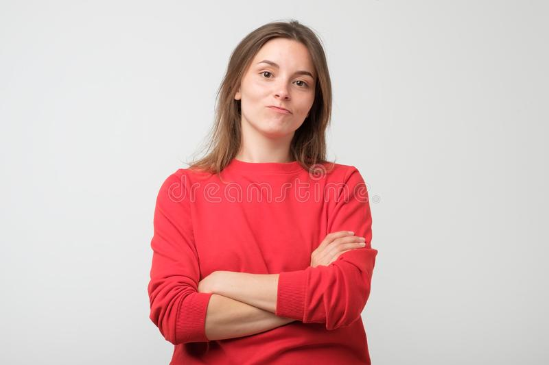 Girl looking at camera, her eyes full of distrust and disappoinmen. Serious young female wearing red pulover looking at camera, her eyes full of distrust and royalty free stock photos