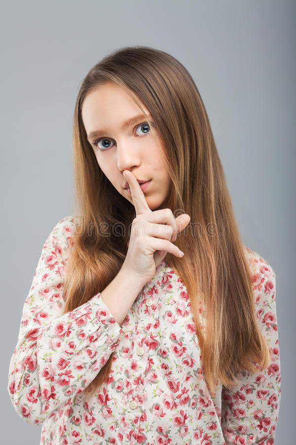 Girl looking at camera, holding finger on her lips royalty free stock photo