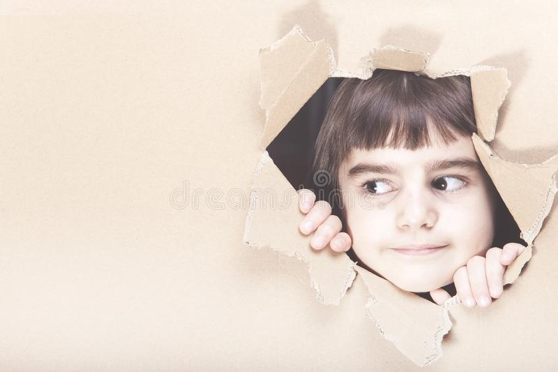 Girl looking through cardboard stock photography