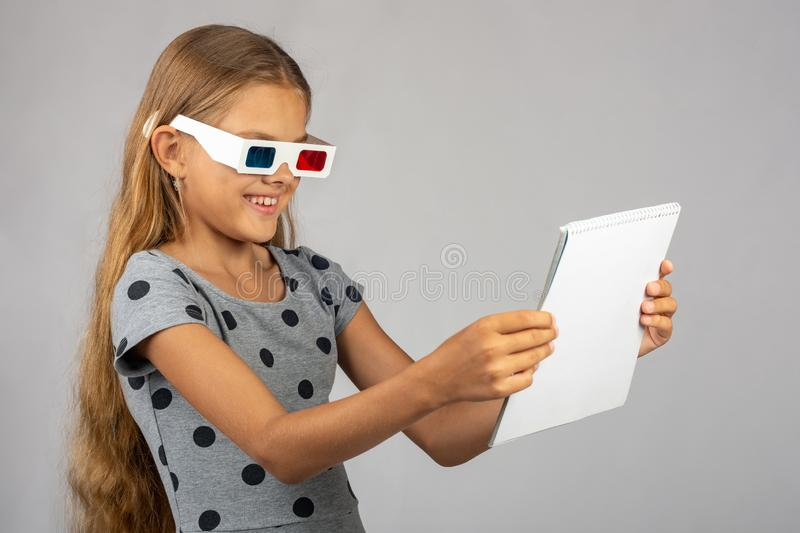 The girl is looking at the colored 3D glasses made using the anaglyph technology of 3D glasses. The girl is looking at the colored 3D glasses made using the stock images
