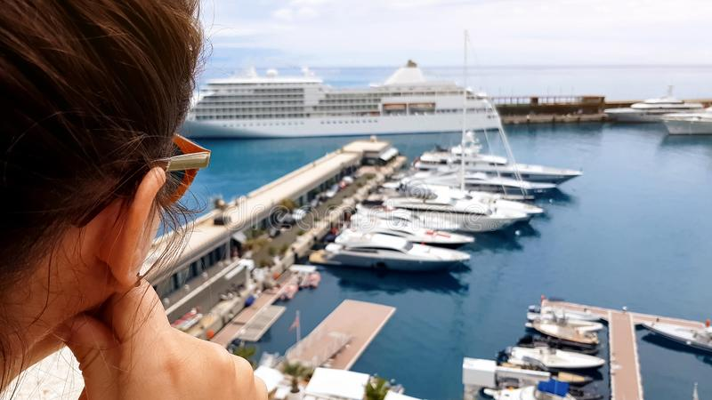 Girl looking at cruise liner from hotel terrace, waiting for embarkation on ship stock image