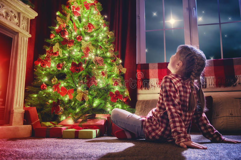 Girl looking at decorations the Christmas tree. stock photography