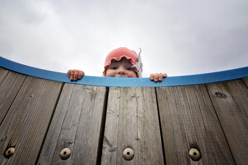 Girl looking down. Over the edge of a wooden climbing frame royalty free stock photos