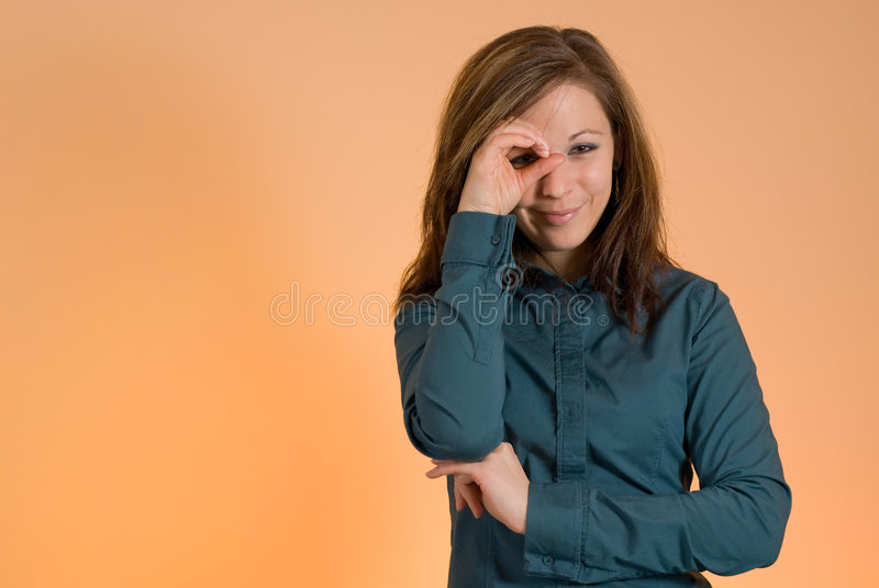 Girl looking through hand. Young attractive girl looking through her hand stock photos